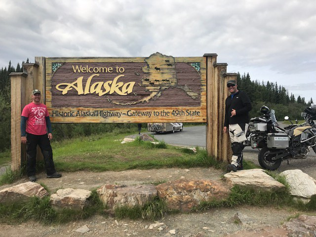 "Two United Pilots smiling in front of the ""Welcome to Alaska"" sign"