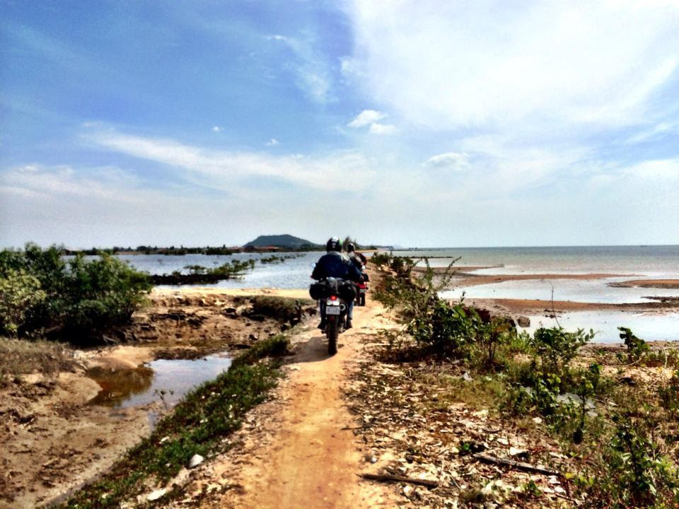 United Employee, Dan Bartlett riding his motorcycle on a dirt path in Southeast Asia.
