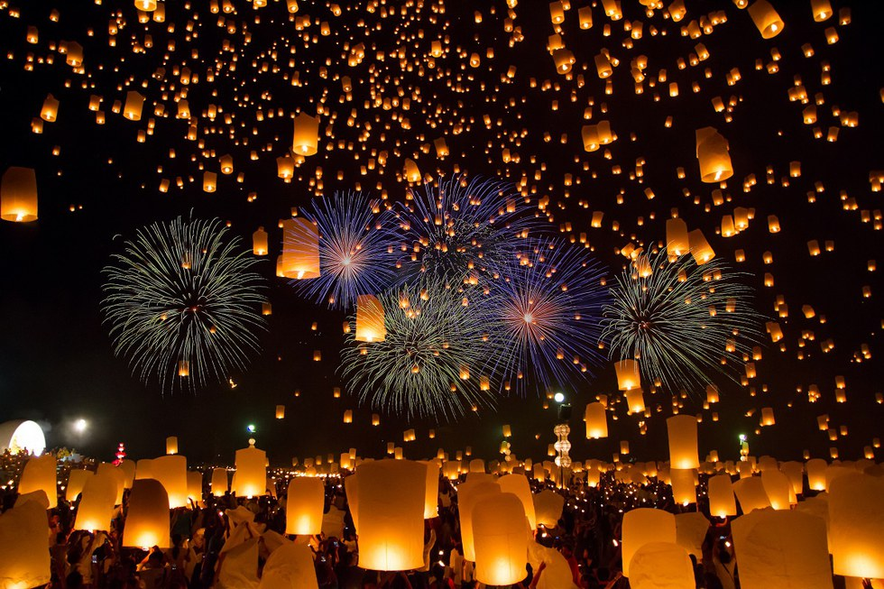 Hundreds of sky lanterns with fireworks in the background.