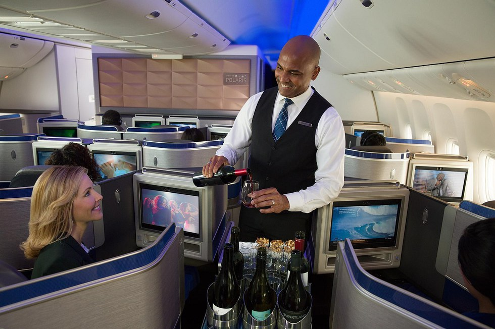 Flight attendant serving drinks on a flight
