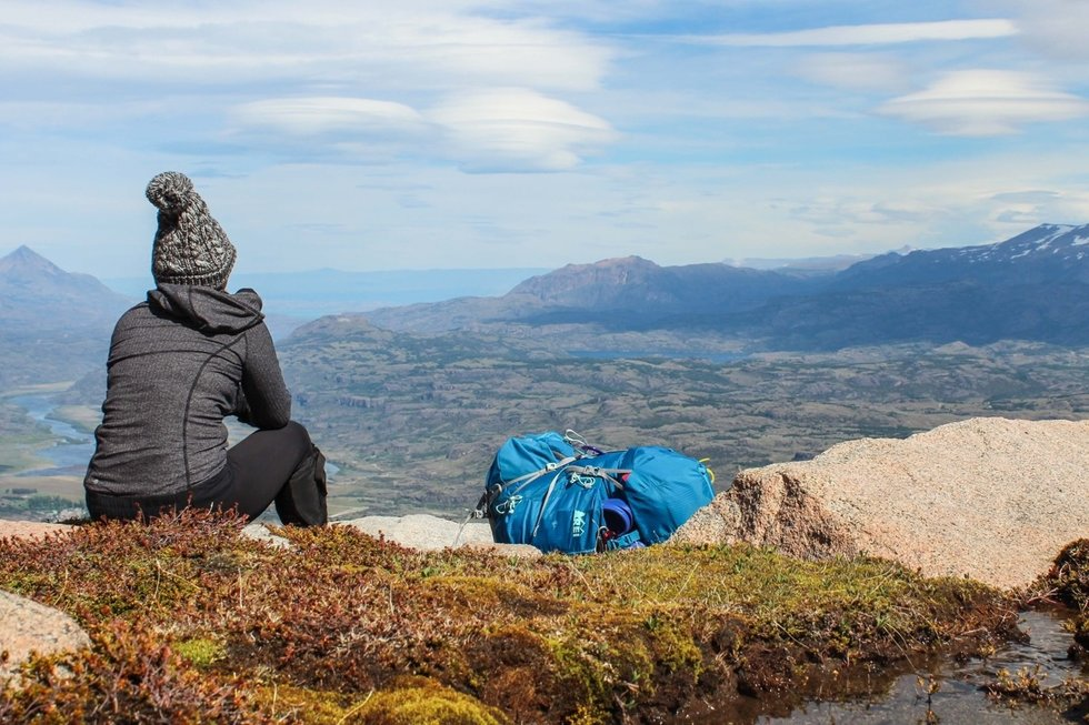 Woman sitting along the edge of a mountain.