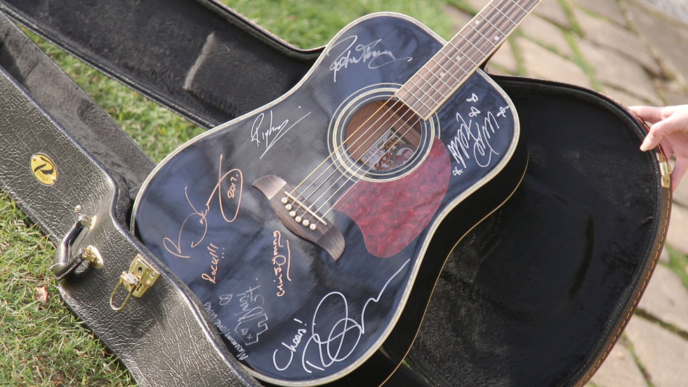 A guitar with multiple famous musician signatures.