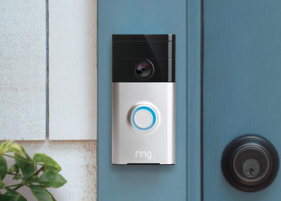 Picture of Ring video doorbell original next to a front door.