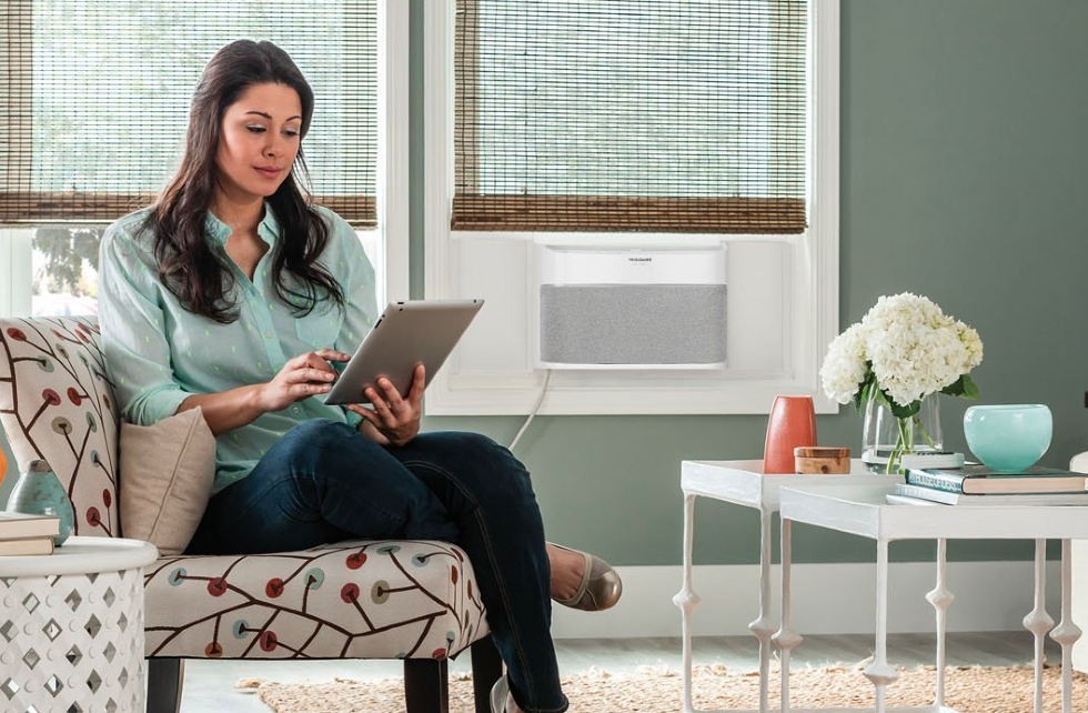picture of a femail in a room with an Frididaire Smart Window Air Conditioner.