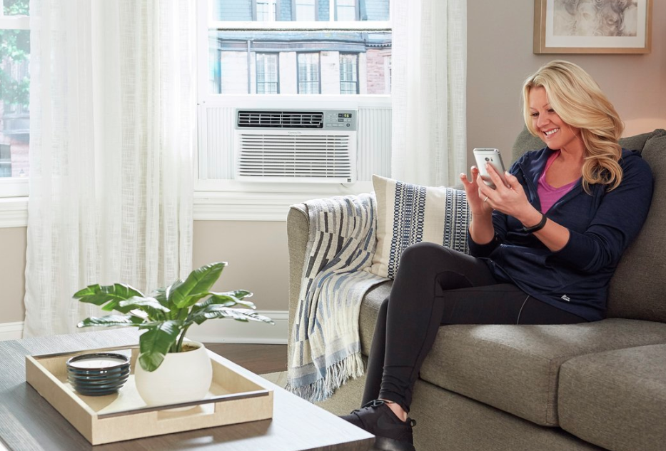 Woman on a couch with an Kenmore 4277087 smart air conditioner in the window.