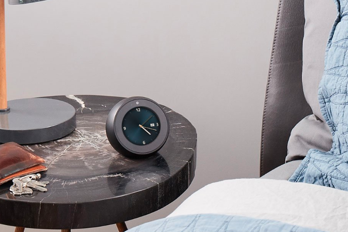 Amazon Echo Spot on a nightstand next to a bed.