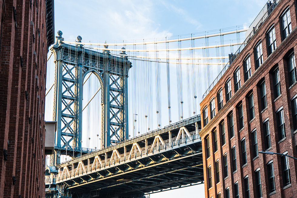 Upward view of the Brooklyn Bridge between buildings.