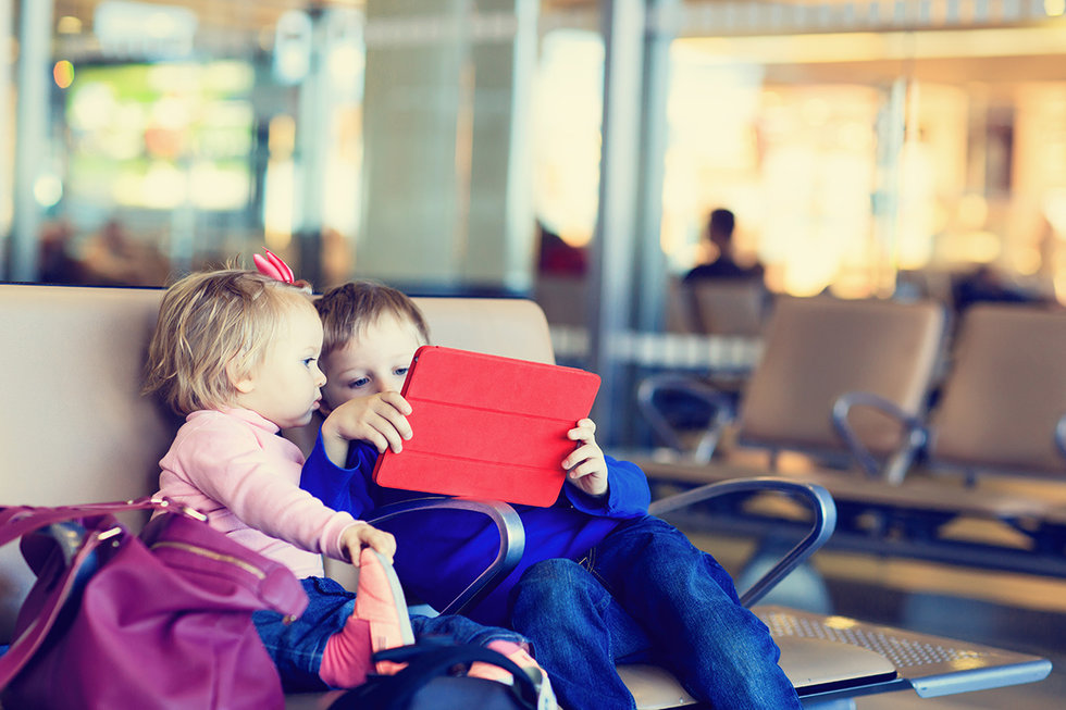 two kids playing on a tablet at the airport
