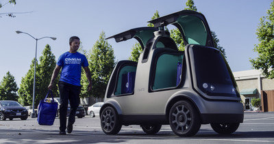 Photo of Kroger delivery person in a Kroger self-driving delivery car.