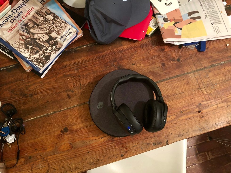Skullcandy venue headphones on a table next to newspapers.