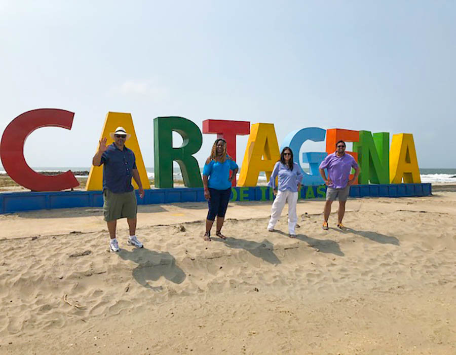 United employee, her husband and friends infront of Cartagena sign.
