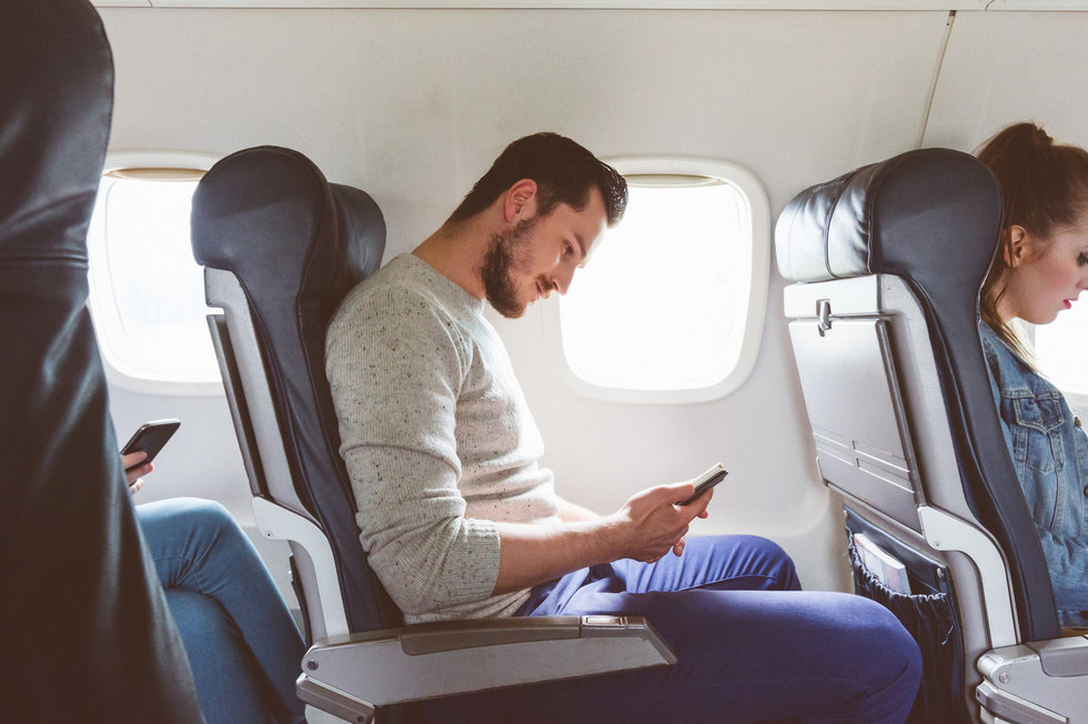 picture of man on airplane looking at his smartphone