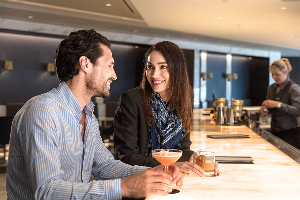 A man and woman enjoy cocktails at the new United Polaris\u00ae lounge