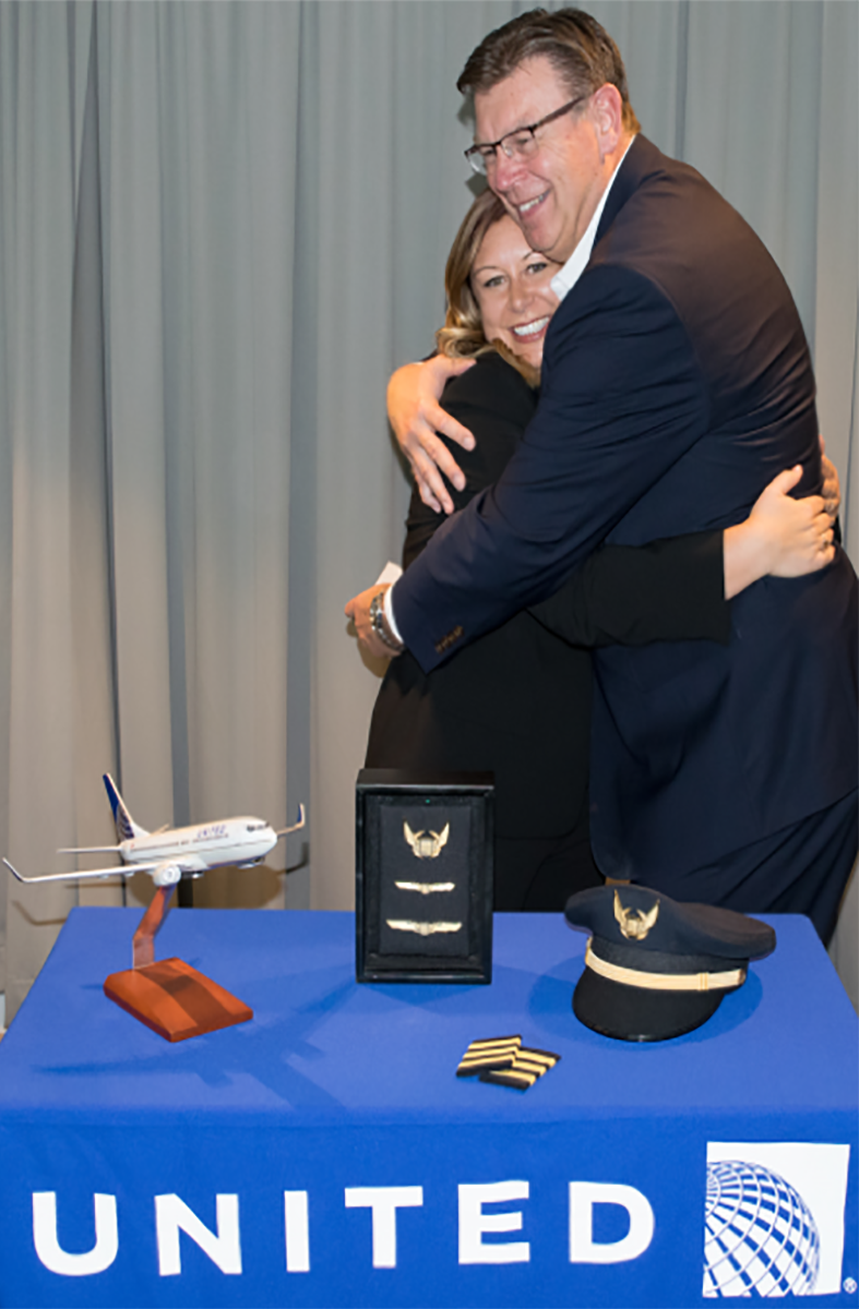 Captain Randy DeMik giving his daughter, First Officer Tamela DeMik her United wings at her new hire ceremony.