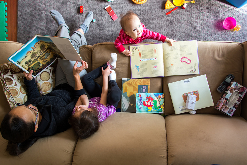 Overhead view of mother and two children looking at books.
