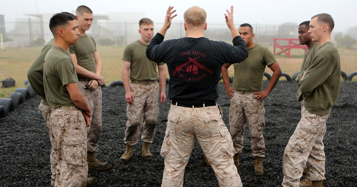 an instructor talks to a group of marines