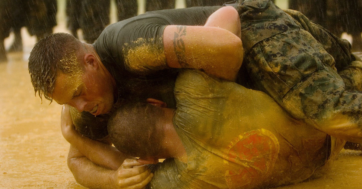 two marines wrestle in dirt