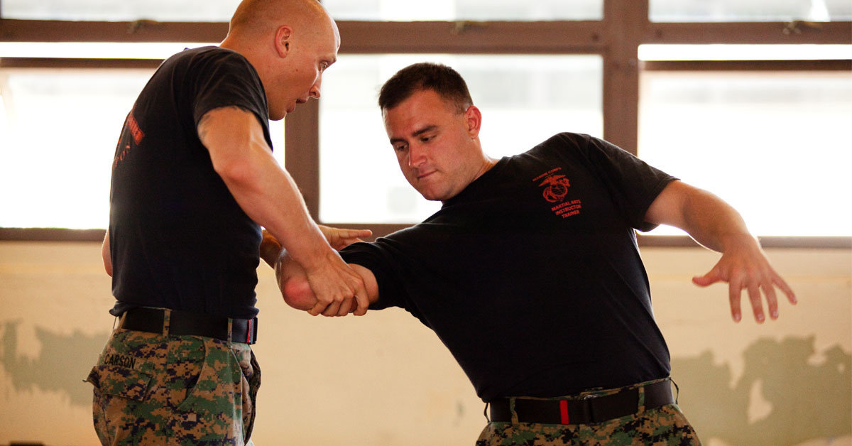 an instructor demonstrates a move on a marine