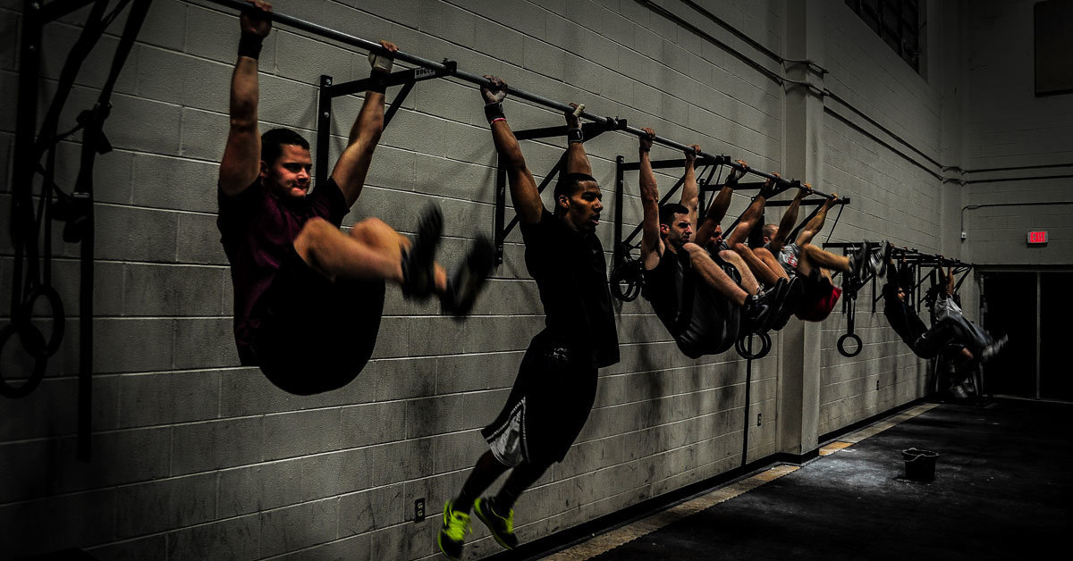 people hanging from pull up bars