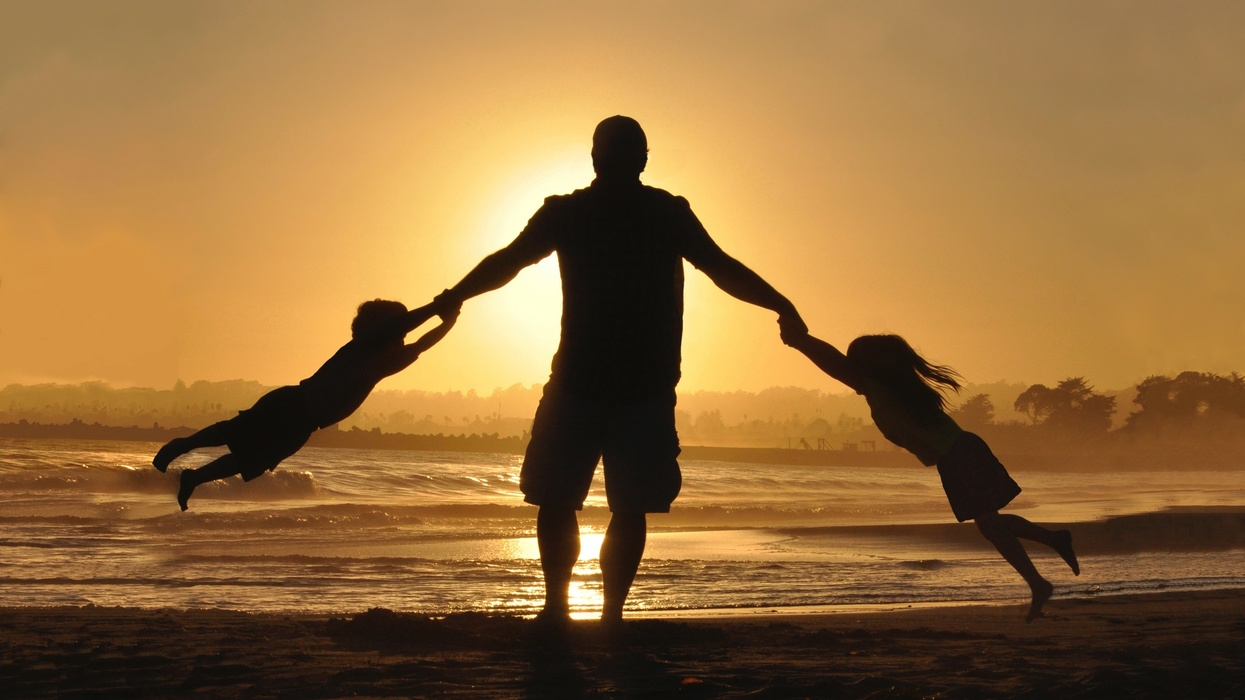 Dad on beach with two kids.