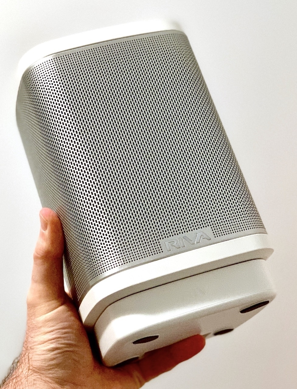 Picture of Riva Concert smart speaker being held up in one hand.