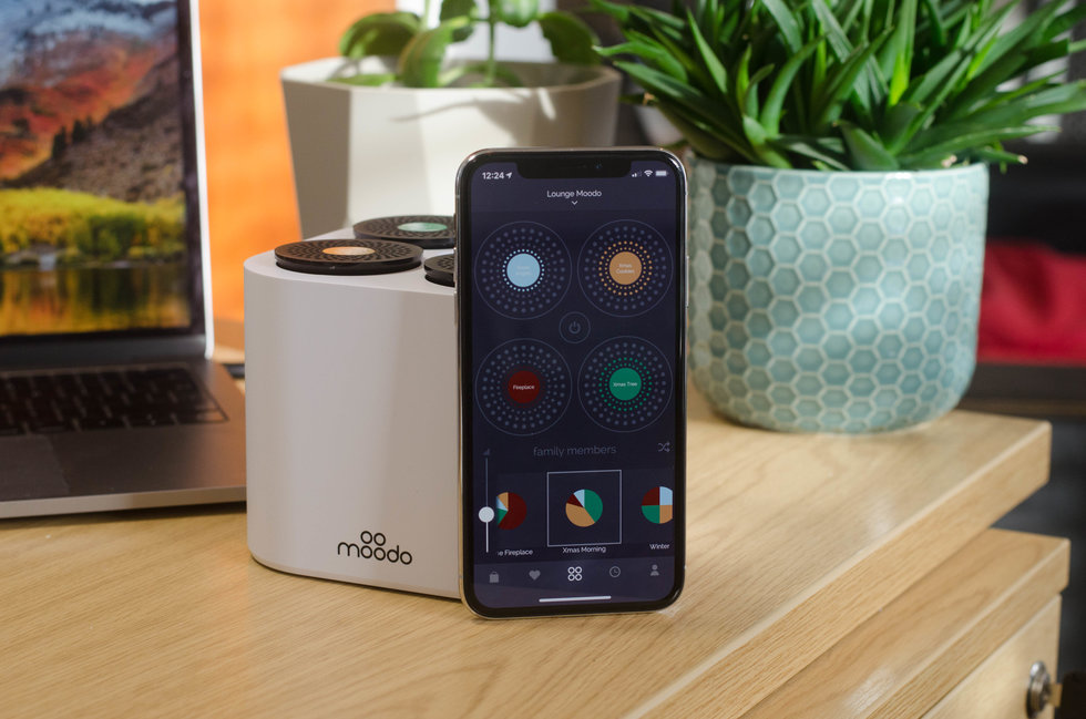 Picture of Moodo Smart Home Fragrance box and smartphone with its app.