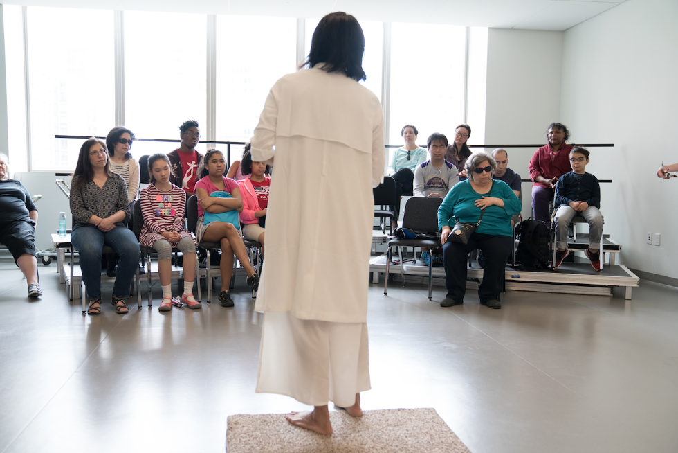 Dance artist Mana Hashimoto is giving a lecture to a group of visually-impaired audience members. She is standing on a platform, wearing a long white dress as the audience listens.