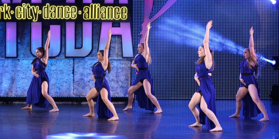 5 dancers on an NYCDA competition stage in a turned-in second position plie, one arm straight up in the air, the other on their stomachs as if taking a breath.