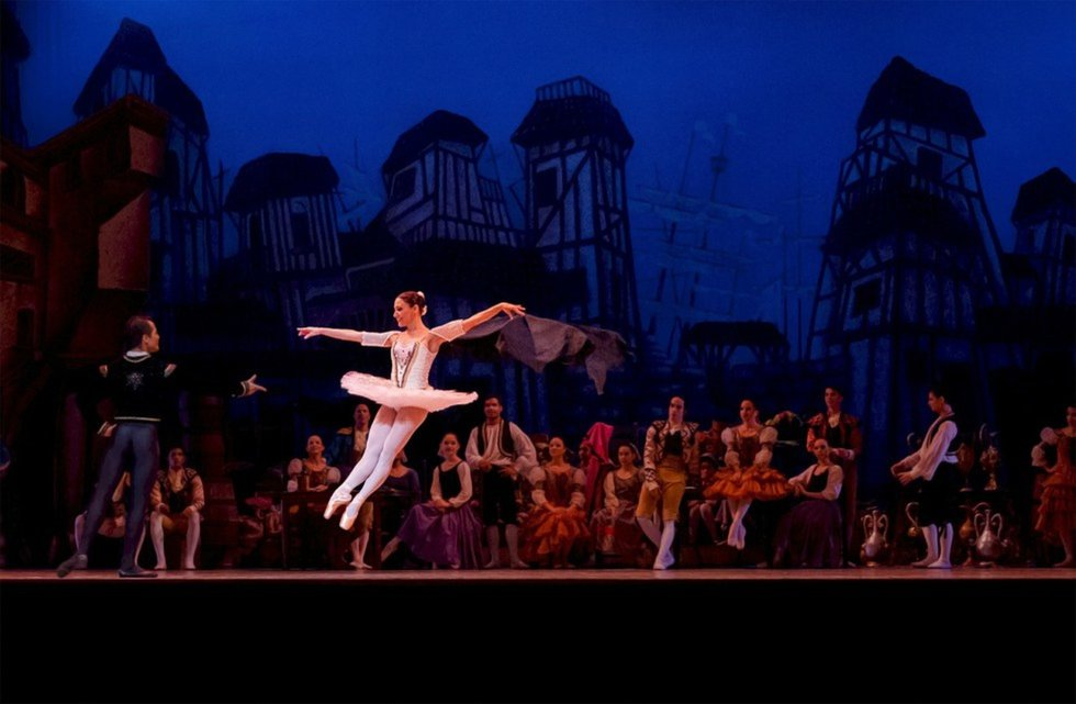 A crowd scene in a classical ballet, with the featured woman mid-jump.
