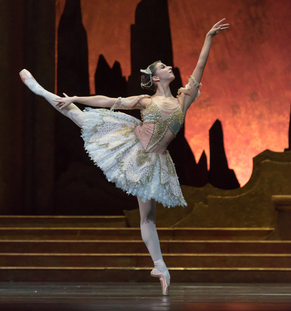 Sasha Mukhamedov in a generous first arabesque, wearing a white and peach tutu.
