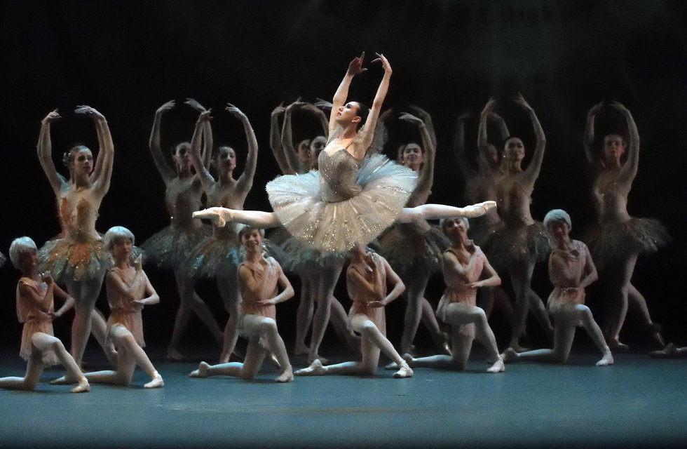 Boylston mid-leap in a classical ballet, with the corps de ballet posed behind her.