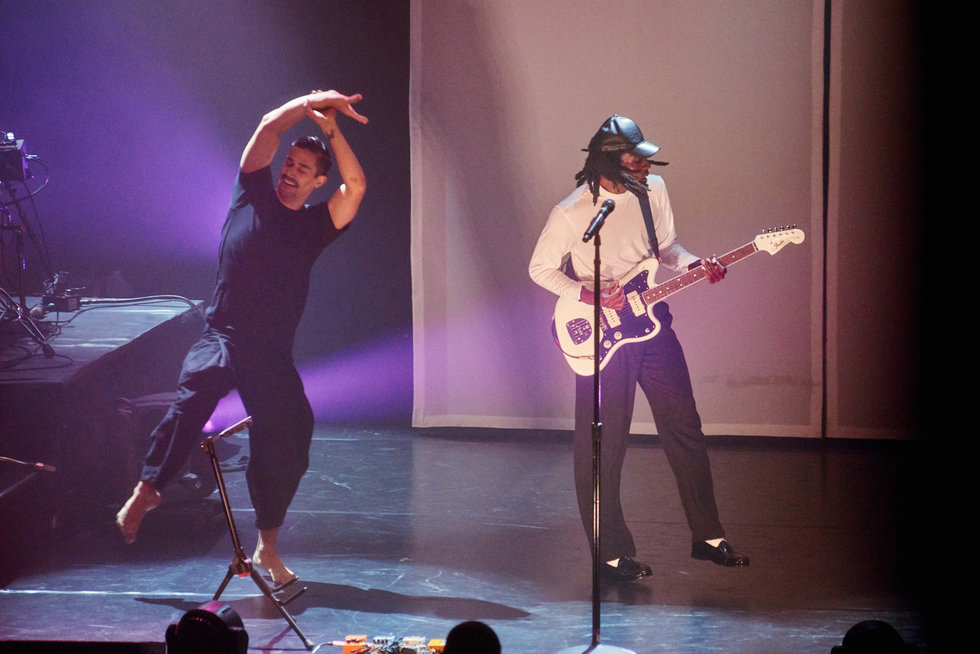 Devont\u00e9 Hynes sings and plays the guitar next to modern dancer Jordan Isadore