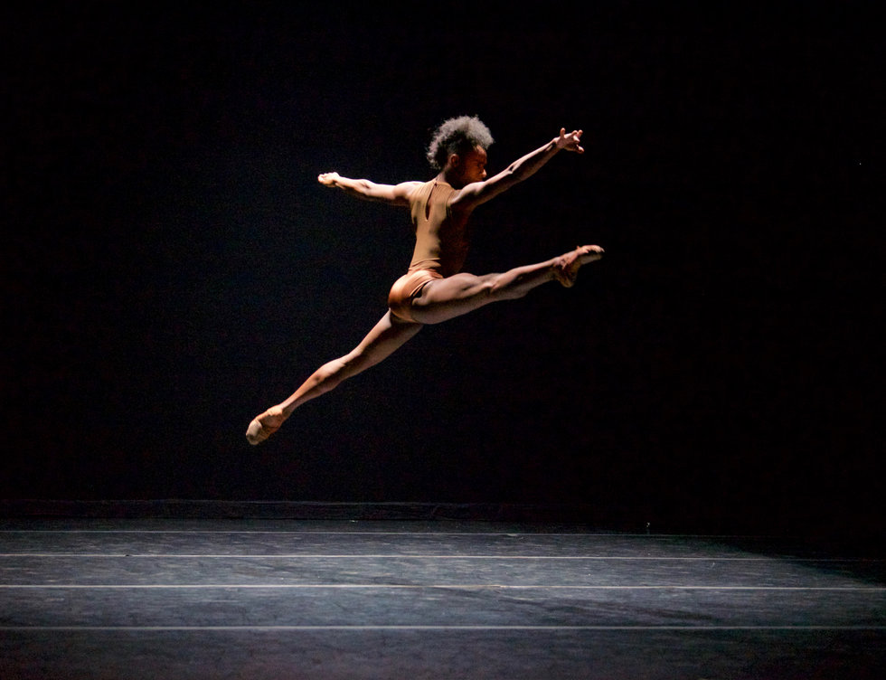 A black dancer flies through the air in a split on a black stage