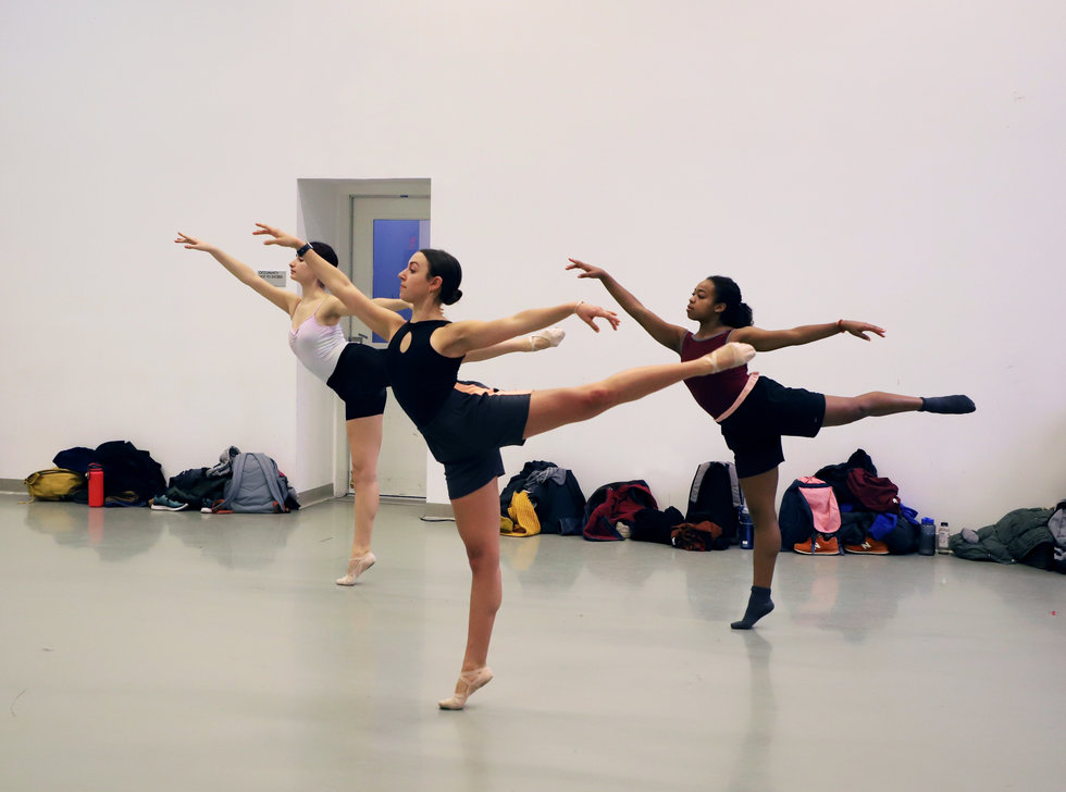Three female ballet dancers perform arabesque in ballet class
