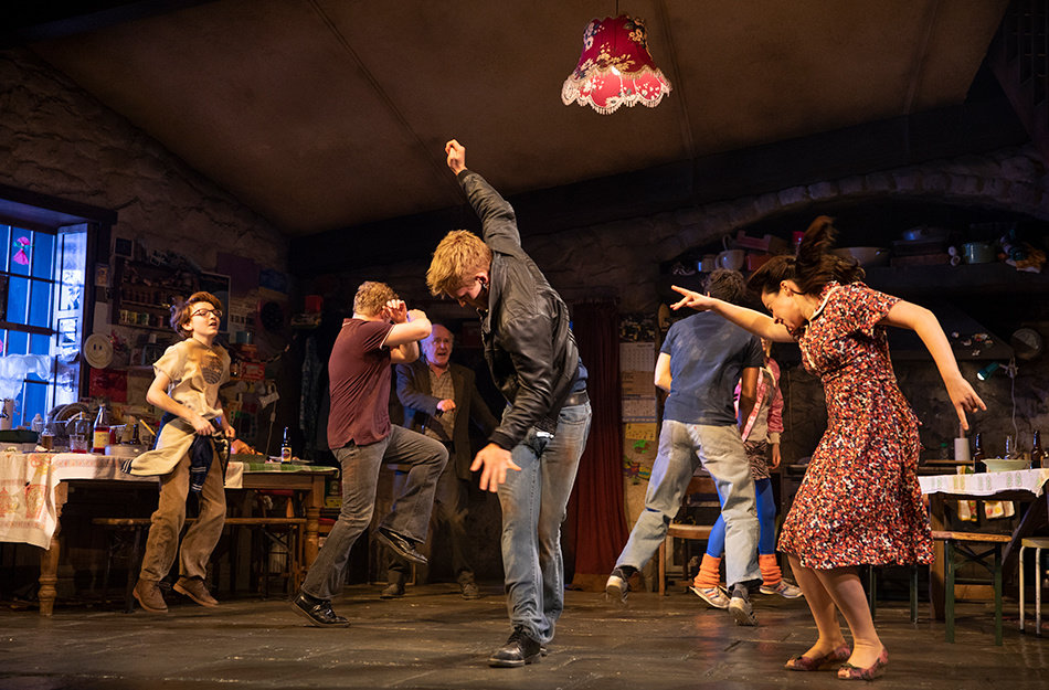 In a large, rustic kitchen, the set of The Ferryman, seven people in casual clothing, men and women, young and old, dance with abandon.