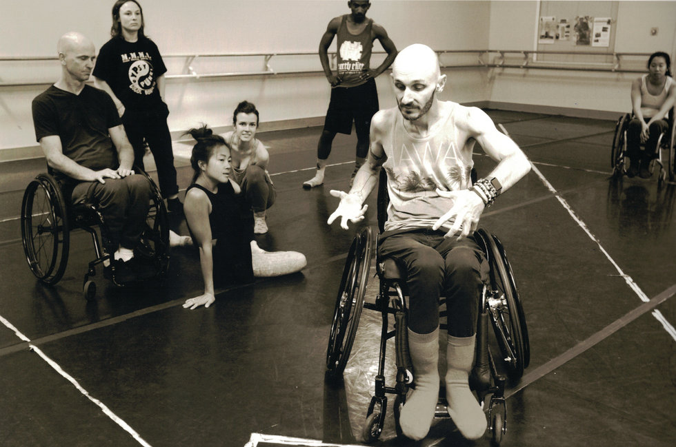 Marc Brew, in a wheelchair, leads a company of dancers, some of whom are also in wheelchairs