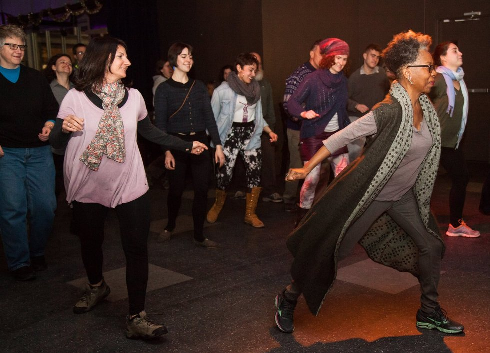Zollar leads a dark room full of adults in a dance class by demonstrating in a low lunge
