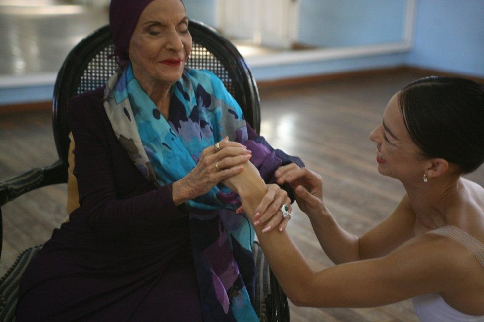 Viengsay Vald\u00e9s holds Alicia Alonso's hands in the dance studio, Valdes from below while Alonso sits in a chair