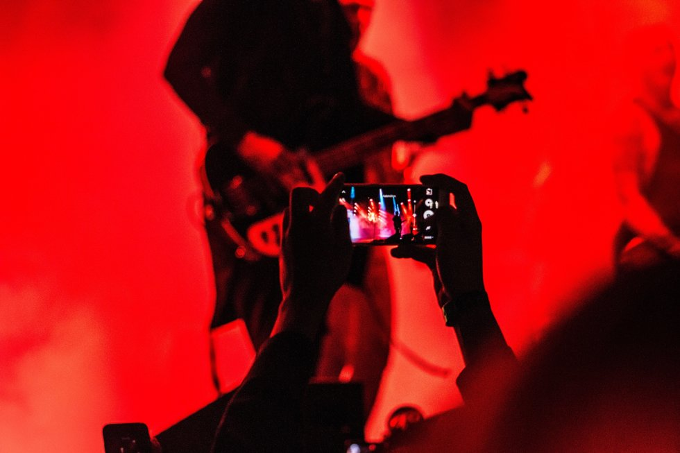 Person in crowd videotaping guitarist