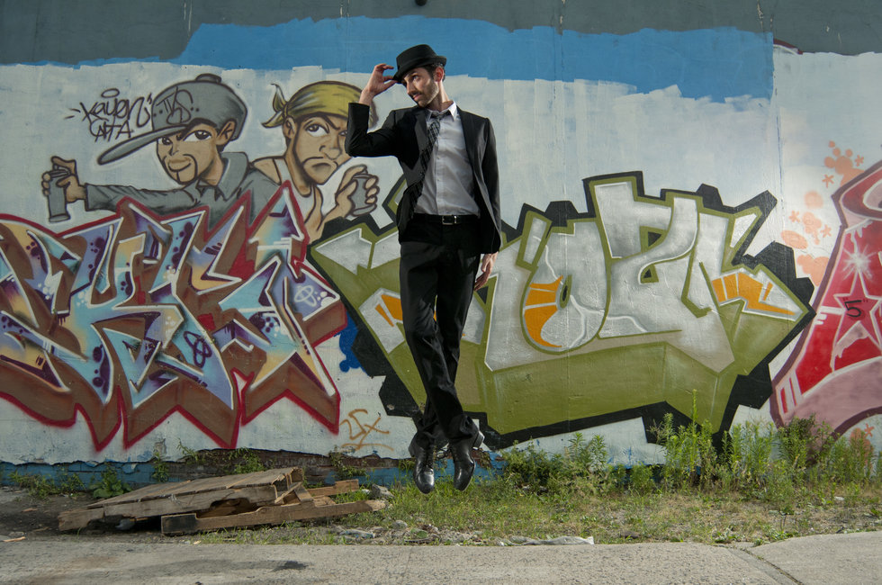 Derek Roland jumps with his feet together in front of a graffitied wall