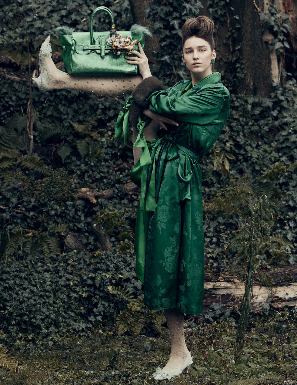 A model in a green dress holds up a purse with her shin, her leg lifted up to her ear