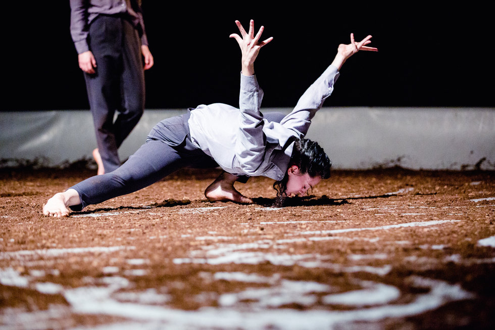 A dancer lunges down with her face almost next to a stage covered in dirt, her fingers splayed as her arms reach behind her