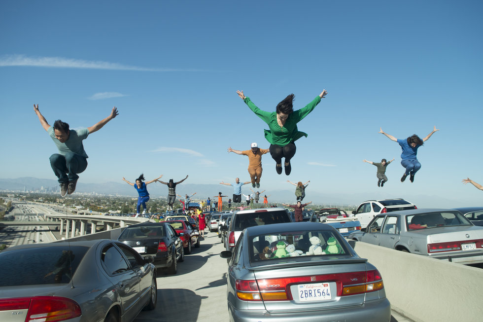 A busy LA highway, with dancers middair jumping on top of the cars.