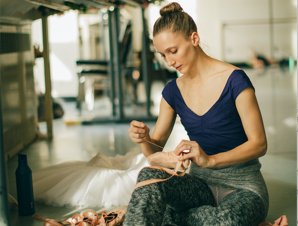 ELizabeth Murphy sews her pointe shoes on the floor of the studio