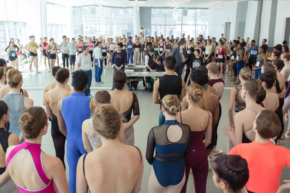 A crowd of auditioning dancers gather in a studio.