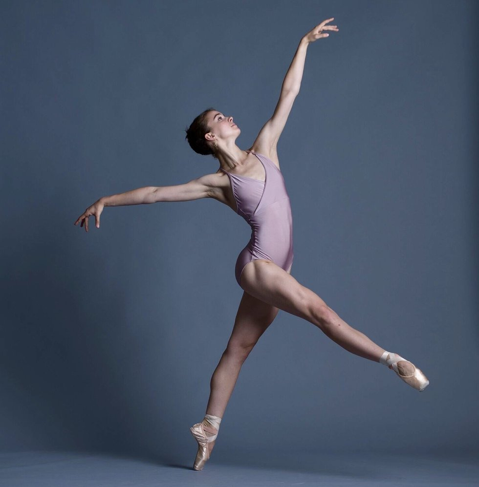 Peabody posed on pointe with one leg extended forwards and her arms reaching long. She is wearing a lavender leotard and the background is gray.