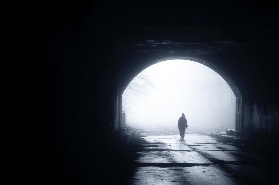 Empty, dark outdoor space with a single person walking