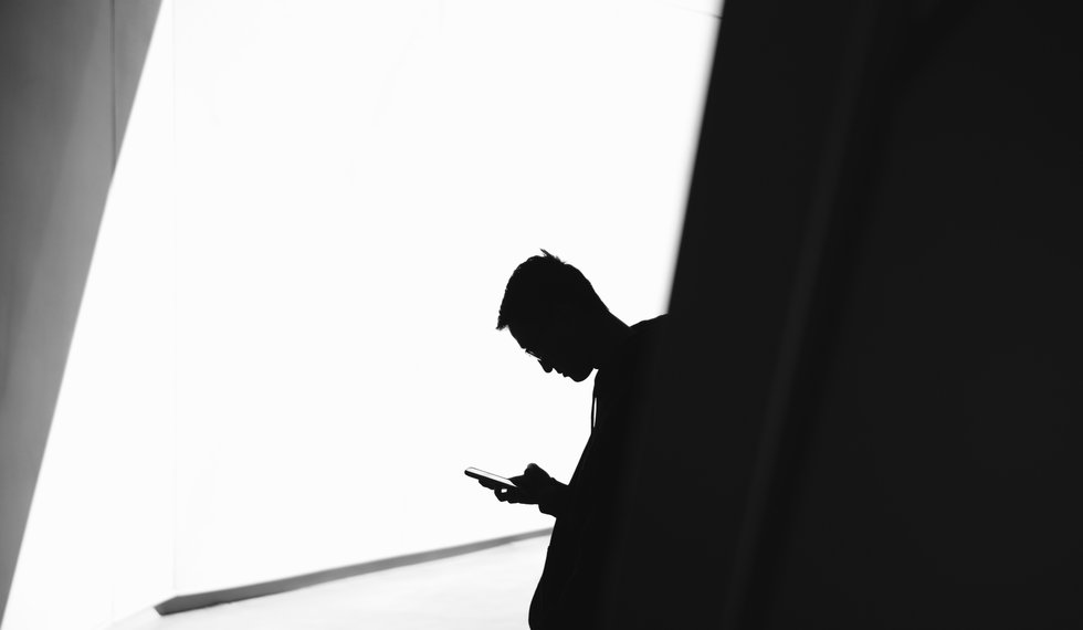 Silhouette of a guy looking down at his phone