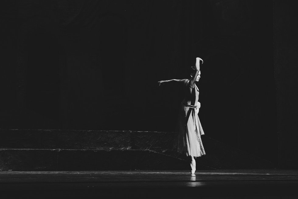 A black and white photo of a dancer on pointe in arabesque