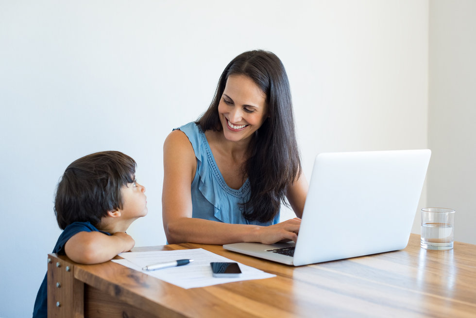 A mother and her child with a contract in front of them near a computer, which can help children and parents follow safety rules